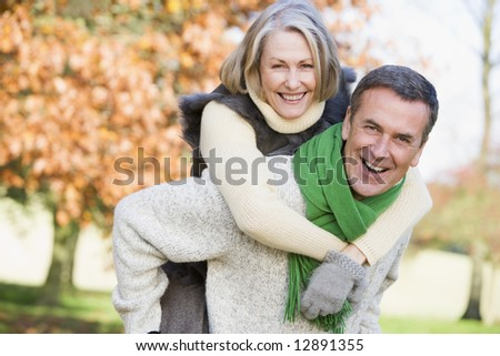 Senior man giving woman piggyback ride through autumn woods - stock photo