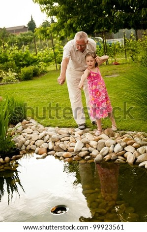 Senior man (grandfather) showing grandchild fish in garden pond - stock photo