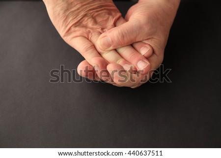 Senior man grasps the numb fingers of his other hand. - stock photo