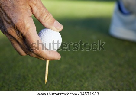 Senior man hand with golf ball and tee