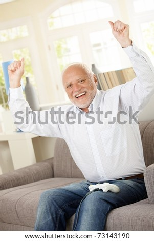 Senior man happy winning computer game, raising arms, laughing, looking at camera.? - stock photo