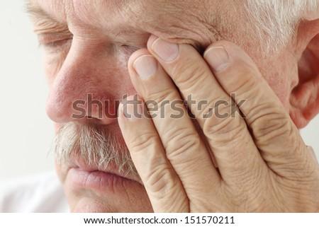 senior man has eyestrain and fatigue - stock photo