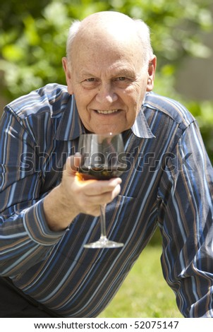 Senior man having a glass of red wine at a picnic outdoors