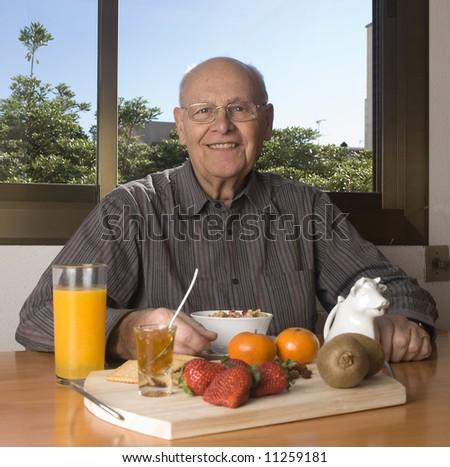 Senior man having a healthy breakfast at home - stock photo