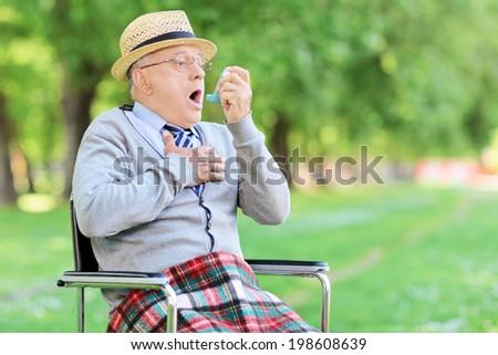 Senior man having an asthma attack in a park - stock photo