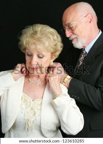 Senior man helping his wife put on a beautiful diamond necklace he has given her as a gift. - stock photo