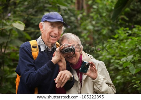 Senior man helps wife look through binoculars in forest - stock photo