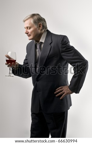 Senior man holding a glass of wine - stock photo