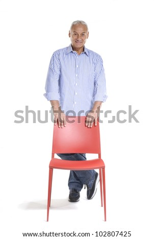 Senior man holding a red chair on white background. - stock photo