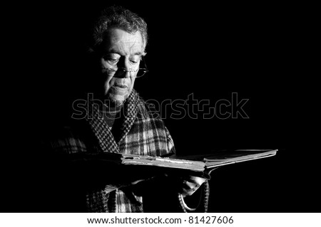 Senior man holding a very old book  in black & white - stock photo