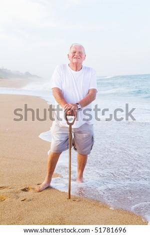 senior man holding a walking cane on beach - stock photo