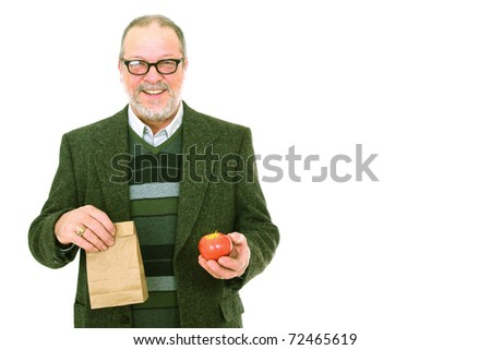 Senior man holding an apple and smiling on white background.  Back to school.