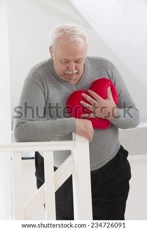 Senior man holding an heart symbol of heart attack - stock photo
