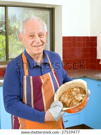 senior man holding an homemade bread in his kitchen - stock photo