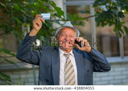 Senior man holding credit card outdoors, laughing, using the phone - stock photo