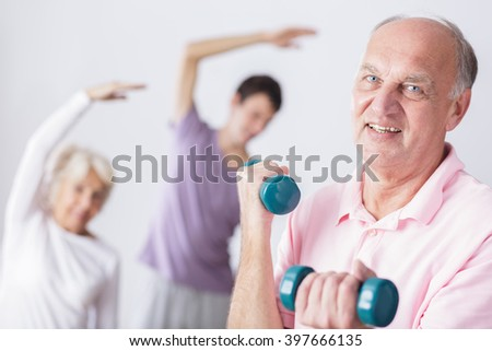 Senior man holding dumbbells and people exercising in background.