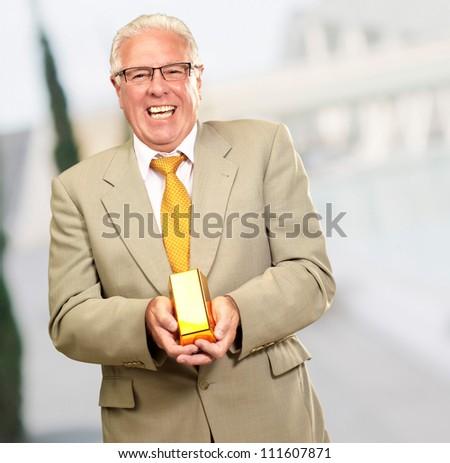Senior Man Holding Gold Bar, Outdoor - stock photo