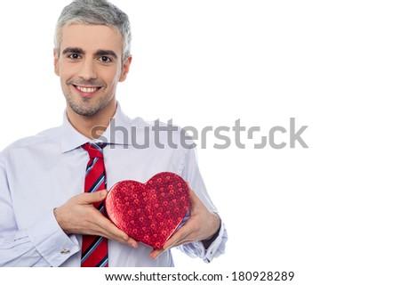 Senior man holding heart shaped gift box - stock photo