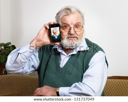 Senior man holding smart phone and showing his picture