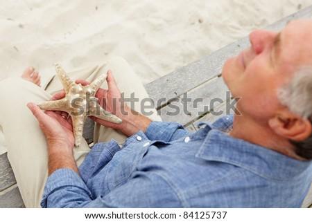 Senior man holding starfish - stock photo