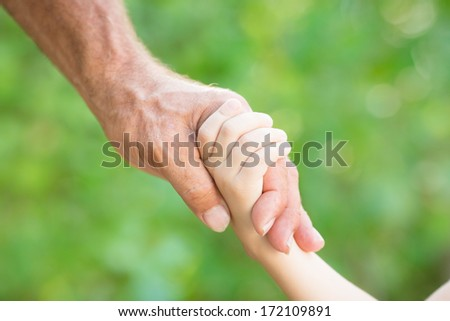 Senior man holding young child by the hands outdoors - stock photo