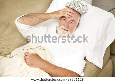 Senior man home sick in bed, with an ice pack on his head.  Could be hangover or illness. - stock photo