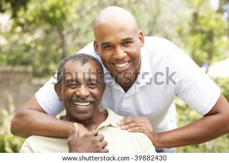 Senior Man Hugging Adult Son - stock photo