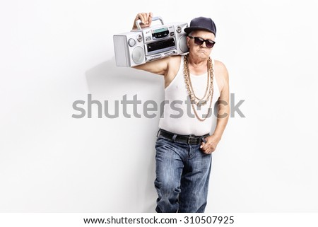 Senior man in a hip-hop outfit carrying ghetto blaster over his shoulder and looking at the camera - stock photo