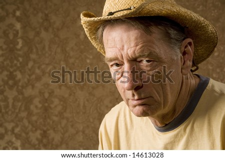 Senior man in a straw hat in front of gold wallpaper