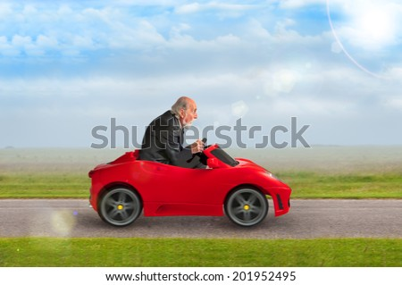 senior man in a suit driving a toy racing car  - stock photo