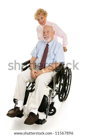 Senior man in a wheelchair with his loving wife pushing him.  Full body on white. - stock photo