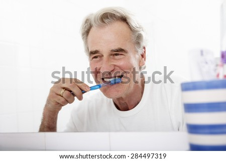 Senior Man In Bathroom Brushing Teeth