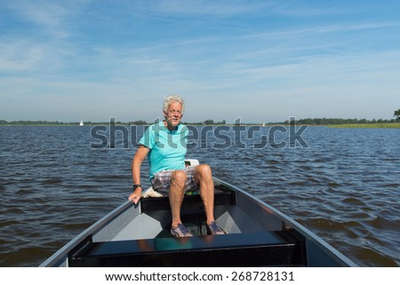 Senior man in boat in Dutch landscape province Overijssel - stock photo