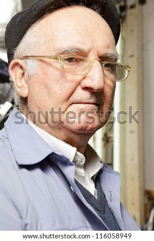 Senior man in cap and eyeglasses looking sideways - stock photo