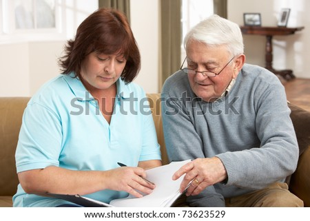 Senior Man In Discussion With Health Visitor At Home - stock photo
