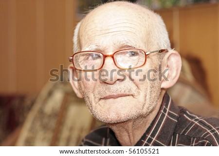 Senior man in eyeglasses looking to camera indoor portrait - stock photo