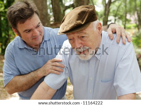Senior man in failing health and his worried middle-aged son.  Focus on Senior man. - stock photo
