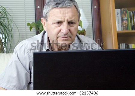 Senior man in front of a PC - stock photo