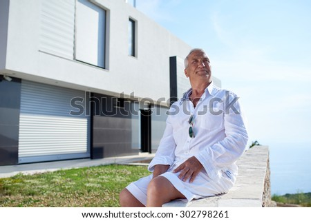 senior man in front of luxury modern home villa - stock photo