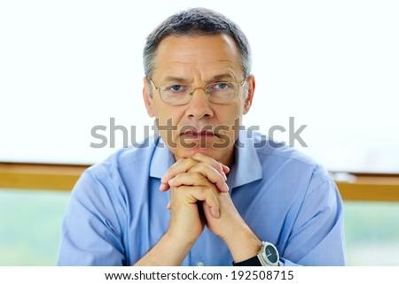 Senior man in glasses looking at camera - stock photo