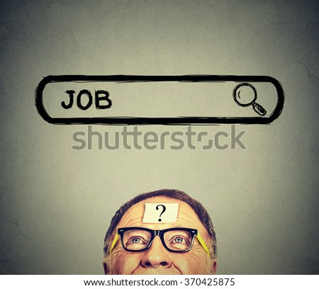 Senior man in glasses looking up searching for a job isolated on gray wall background. Employment job market concept  - stock photo