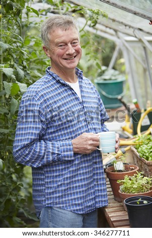 Senior Man In Greenhouse With Hot Drink