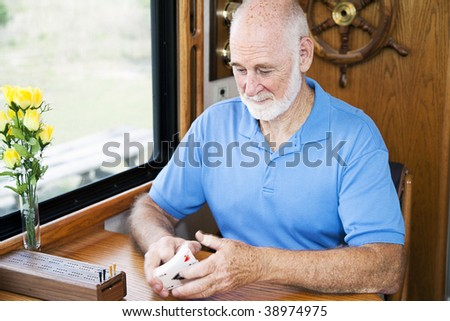 Senior man in his RV, shuffling cards to play cribbage.  Motion blur on the cards.