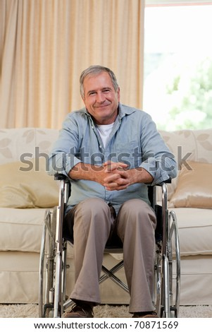 Senior man in his wheelchair at home - stock photo