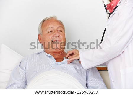 Senior man in hospital bed getting auscultating with stethoscope from a nurse - stock photo