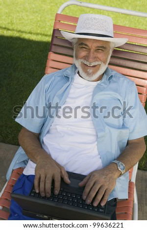 Senior Man in Lawn Chair Using Laptop