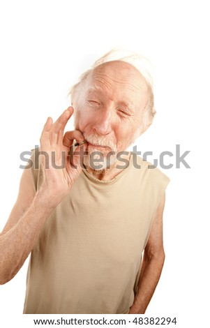 Senior man in ragged shirt smoking cigarette stub or marijuana reefer - stock photo