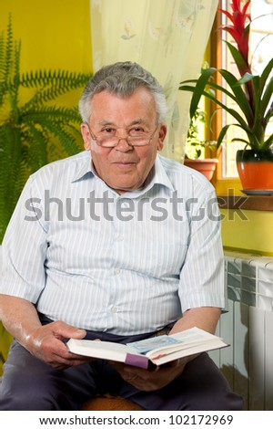 Senior man in 80s reading book at home