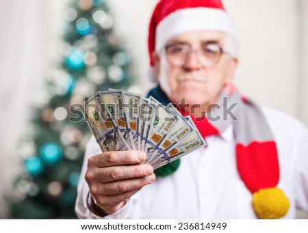 Senior man in Santa's hat holding money on Christmas background, hand in focus - stock photo