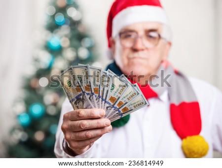 Senior man in Santa's hat holding money on Christmas background, hand in focus - stock photo